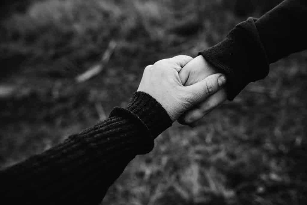 Imagem preta e branca de duas mãos dadas