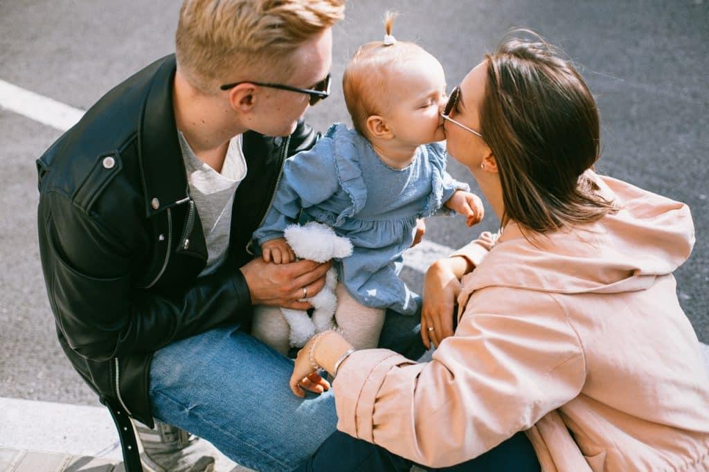 Homem e mulher brancos segurando bebê branca.