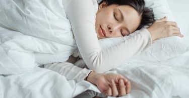 Mulher dormindo de lado em uma cama com lençóis brancos