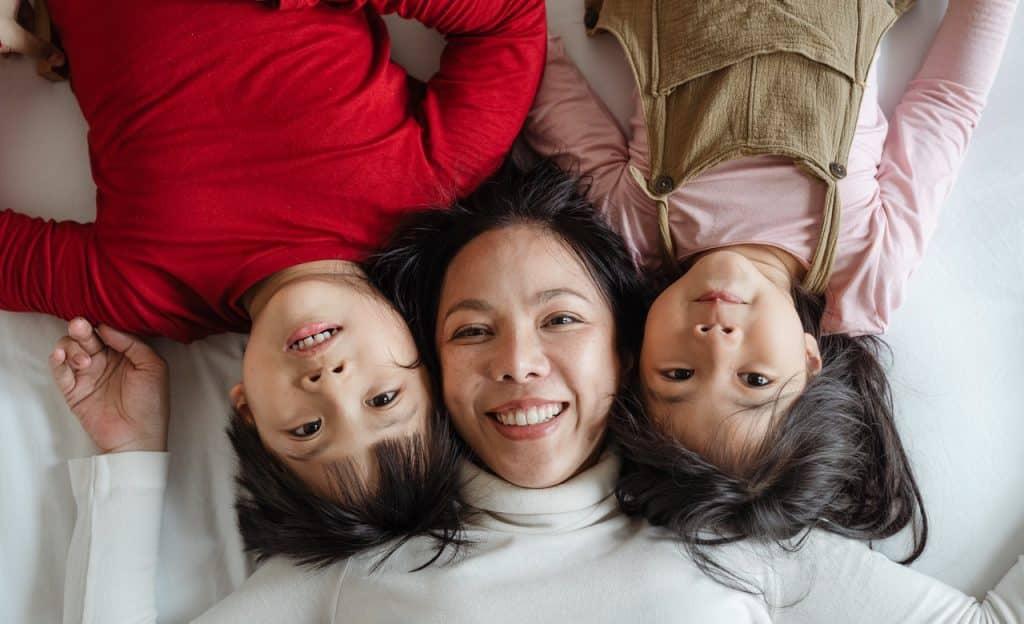 Mulher deitada em cama entre duas crianças.