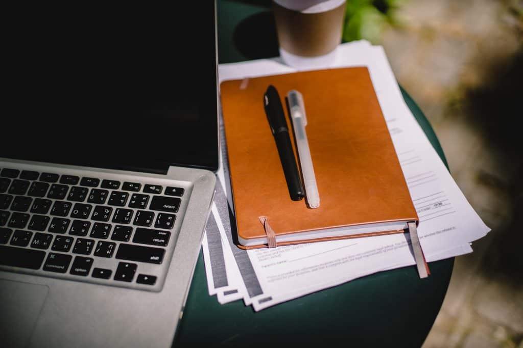 Duas canetas em cima de uma agenda com um laptop ao lado