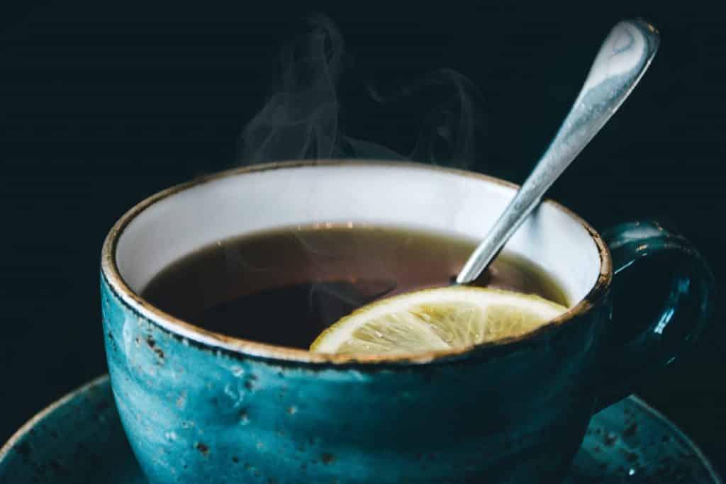 Xícara cheia de chá com uma rodela de limão. Há também uma colher no líquido.
