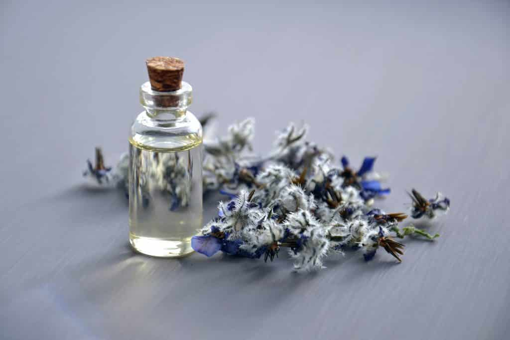 Flores com garrafa de óleo natural ao lado.
