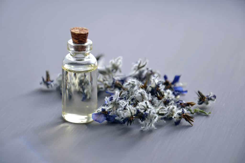 Vidro de óleo essencial com uma flor lilás atrás