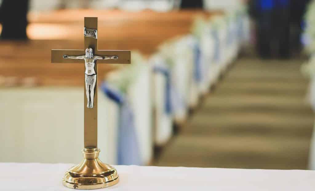 Cruz e, ao fundo, interior de uma igreja.