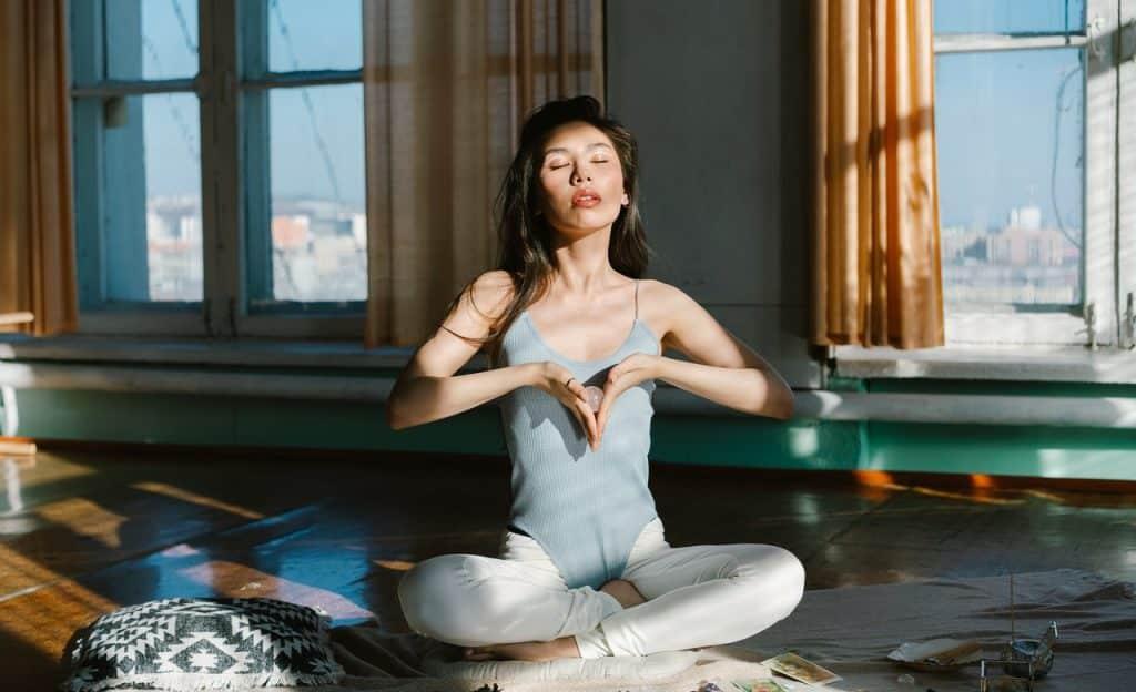 Mulher sentada no chão com as mãos próximas ao peito formando um triângulo invertido. Ela está com os olhos fechados e em um ambiente interno.