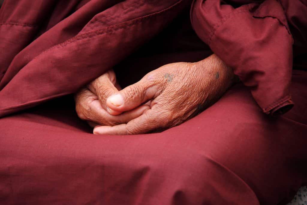 Mãos sobrepostas de um monge budista