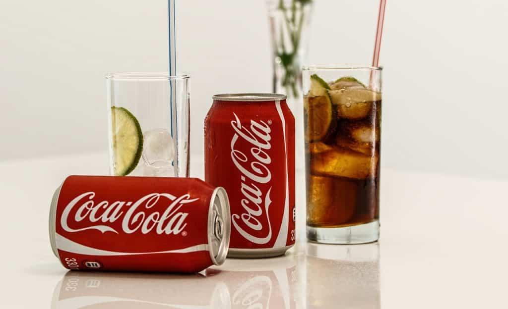 Duas latas de refrigerantes de cola entre dois copos, um deles com gelo, limão, um canudo e o outro em igual conteúdo, com a adição do líquido do refrigerante. Os objetos estão sobre uma superfície branca.