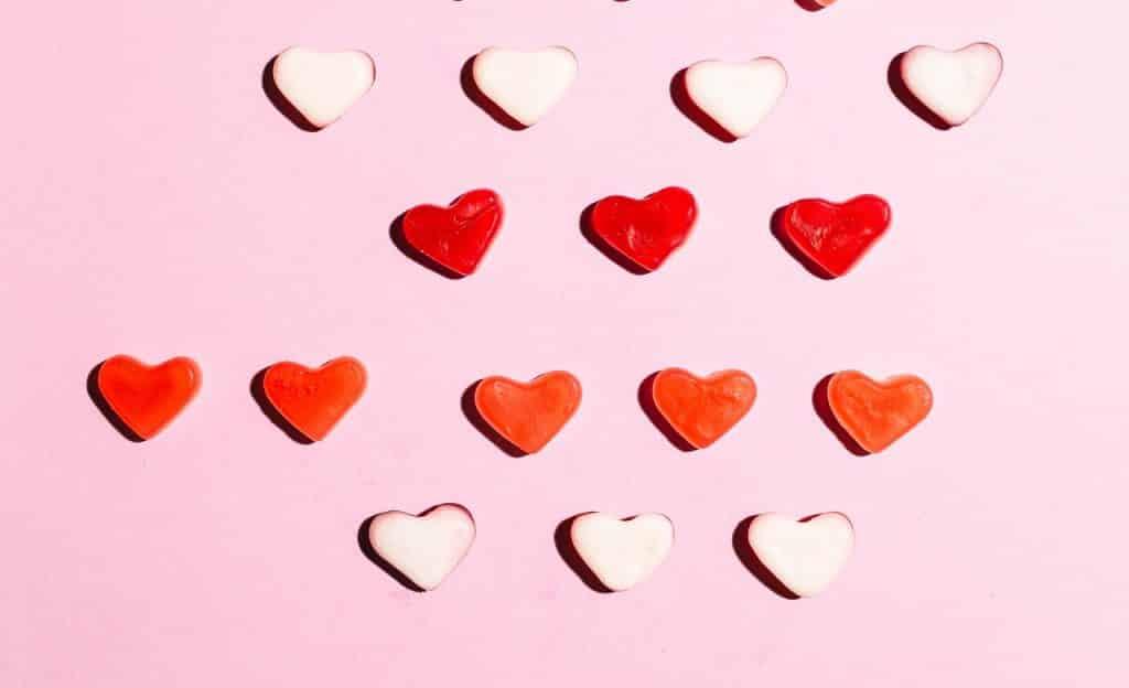 Corações enfileirados sobre fundo rosa.