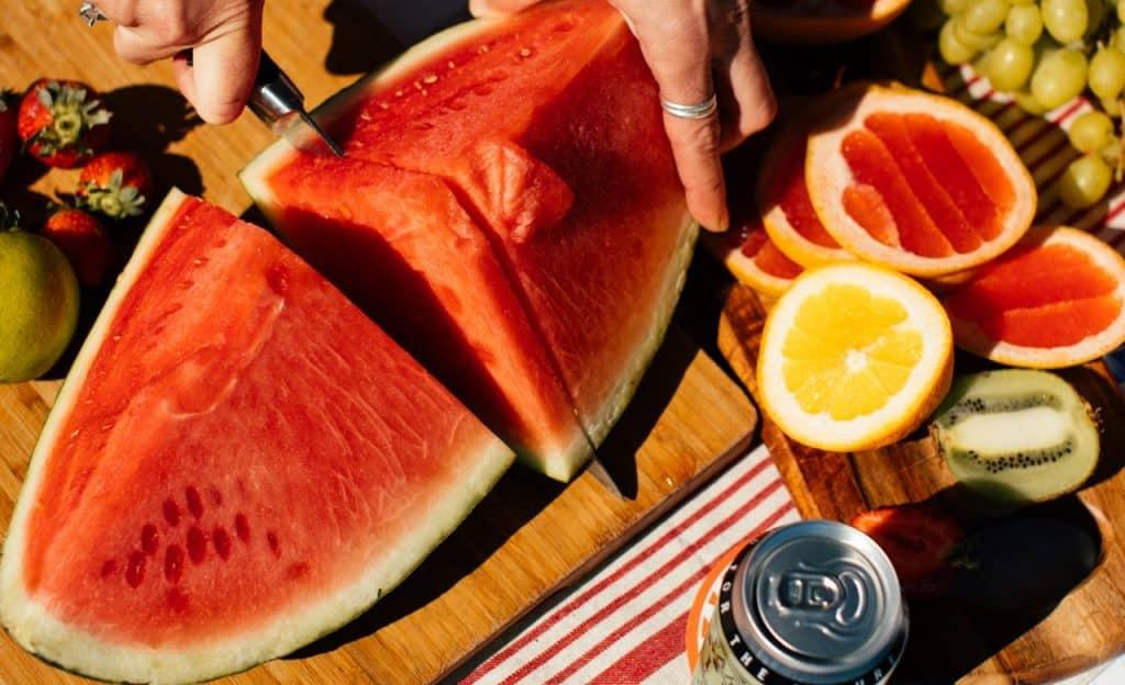 Mão corta melancia que está sobre mesa de madeira. Ao lado, também há outras frutas e uma lata fechada.