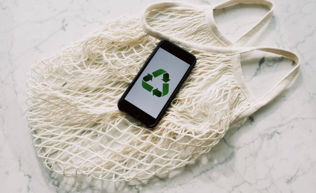 Celular com sinal de reciclagem sobre bolsa de rede.