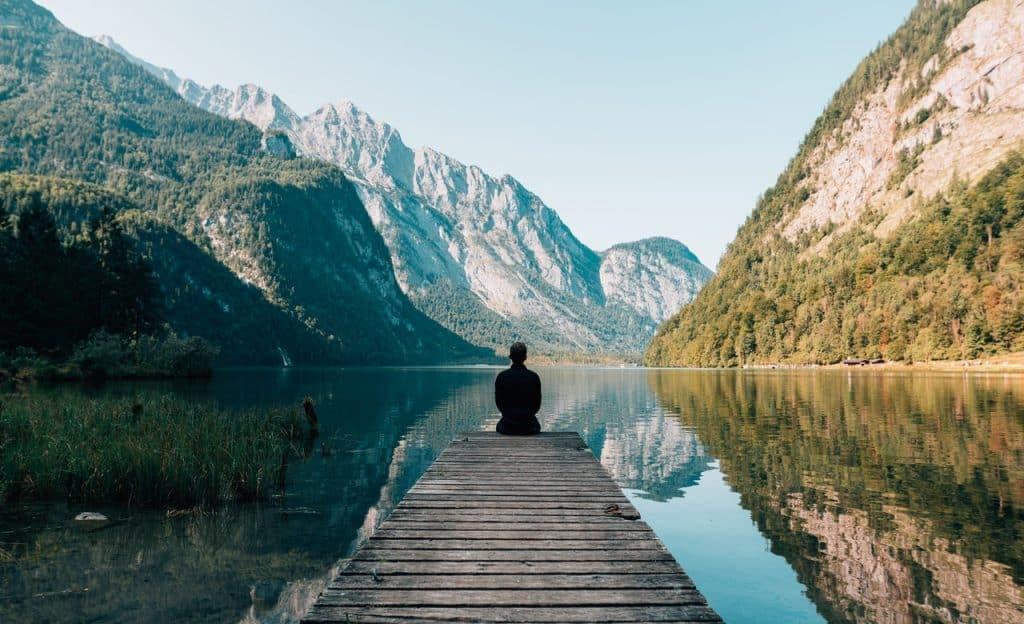Homem sentado à beira de cais. Ao fundo, há montanhas.