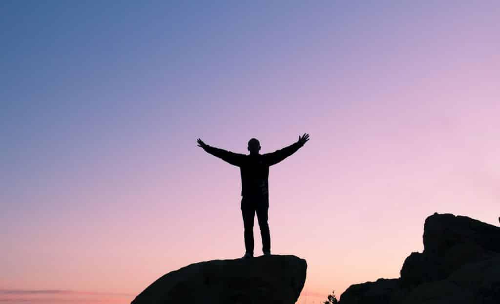 Homem em pé sobre pedra. Ele está com os braços abertos e erguidos.