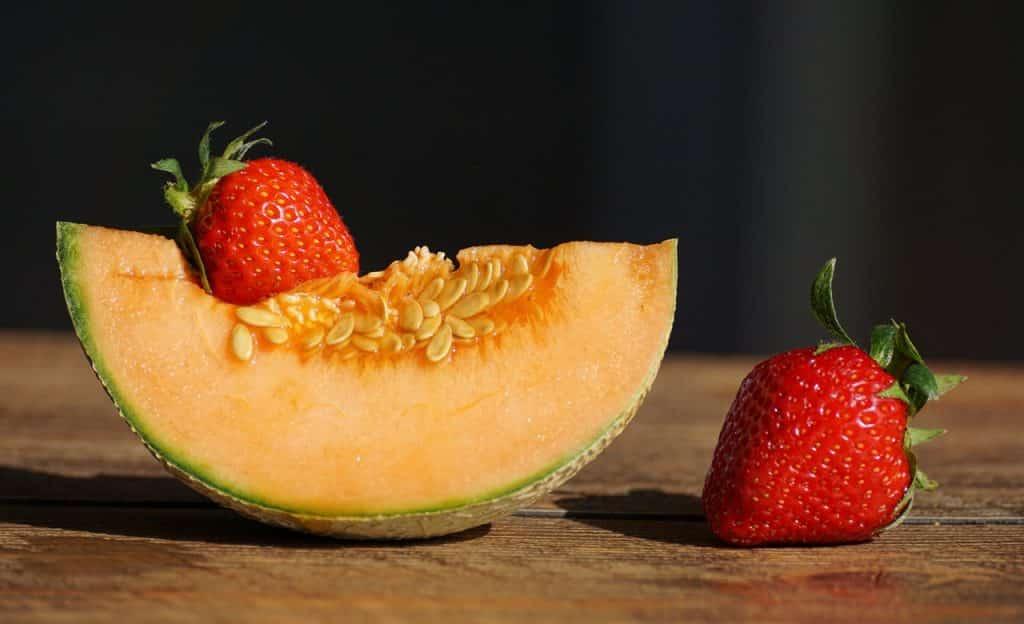 Fatia de melão e dois morangos sobre mesa de madeira.