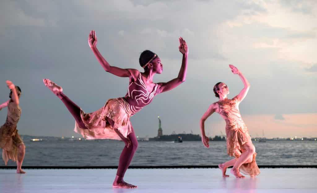 Três mulheres dançam em superfície próxima de um lago.