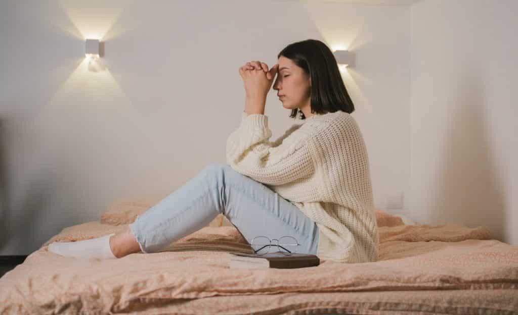 Mulher sentada em cama pratica oração.