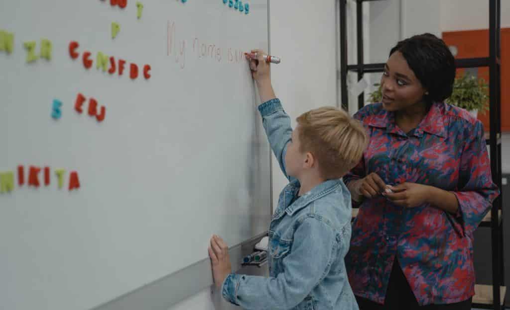 Professora ao lado de aluno que escreve em quadro.