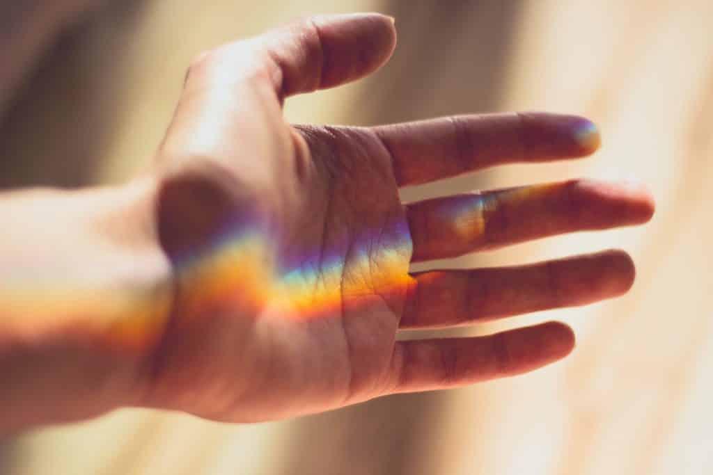 Mão com um reflexo formando um arco-íris