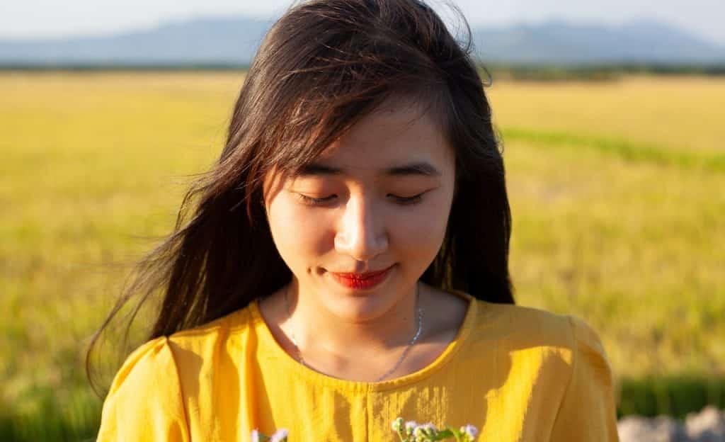 Mulher sorri discretamente. Seus olhos estão fechados, a cabeça inclinada para baixo e os cabelos ao vento. O cenário é externo e de campo.