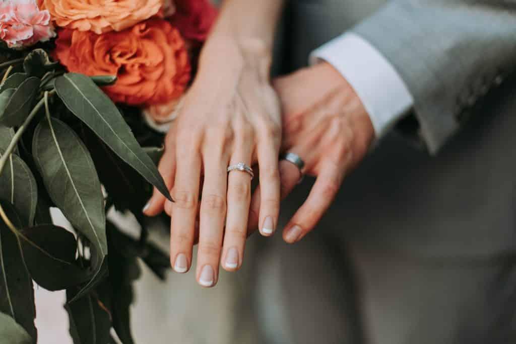 Mãos brancas juntas com aliança.