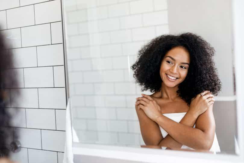 Mulher negra se abraçando em frente ao espelho.