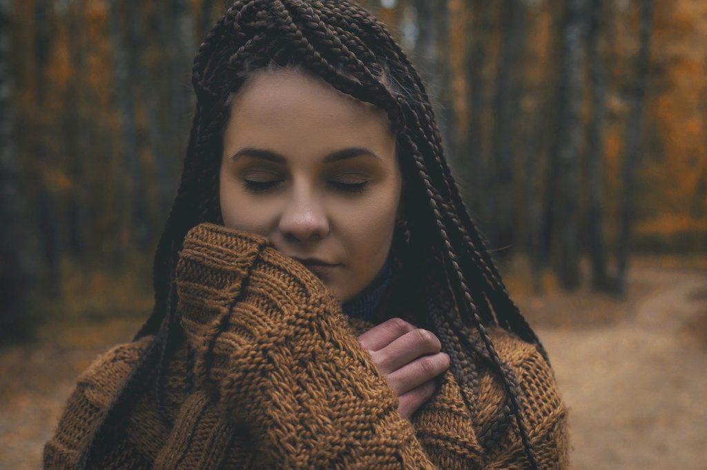 Mulher em uma floresta se sentindo conectada com a natureza