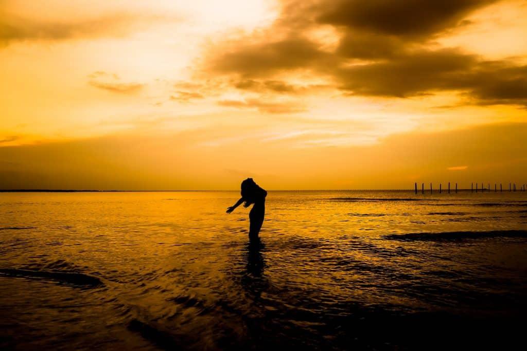 Silhueta de mulher na praia.