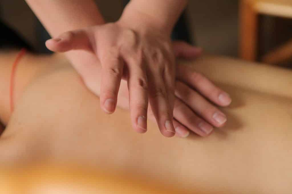 Imagem de uma pessoa deitada de costas recebendo uma massagem de quiropraxia em suas costas.