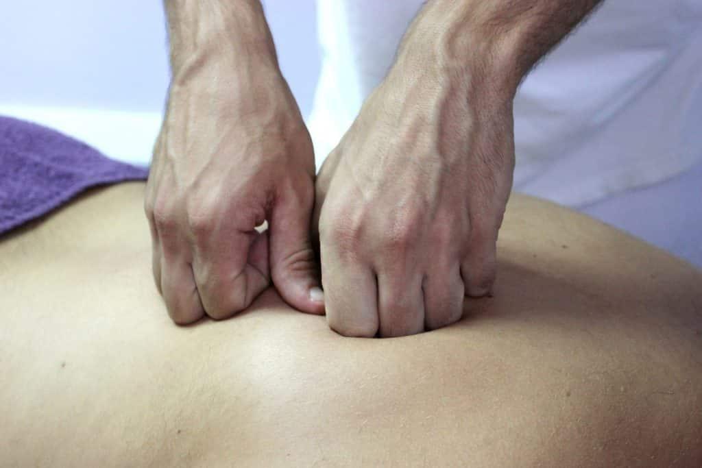 Imagem das costas de uma pessoa. Parte dela está coberta com uma toalha na cor roxa. A pessoa está recebendo uma massagem de quiropraxia nas costas.