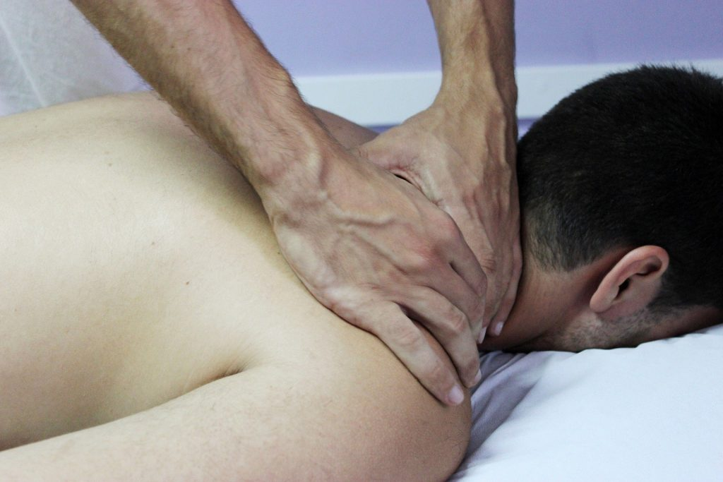 Imagem de um homem de cabelos pretos e curtos deitado de costas sobre uma maca forrada com um lençol na cor branca. Ele está recendo em seus ombros o tratamento de quiropraxia. Duas mãos masculinas estão impostas sobre essa região.