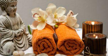 Imagem de um kit para uso na quiropraxia composto por duas toalhas na cor laranja, pedra, flores brancas, velas e a estátua do Buda.