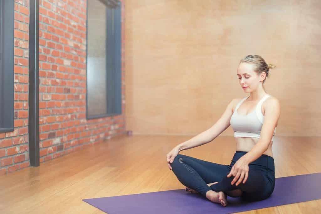 Mulher de pernas cruzadas meditando em um salão
