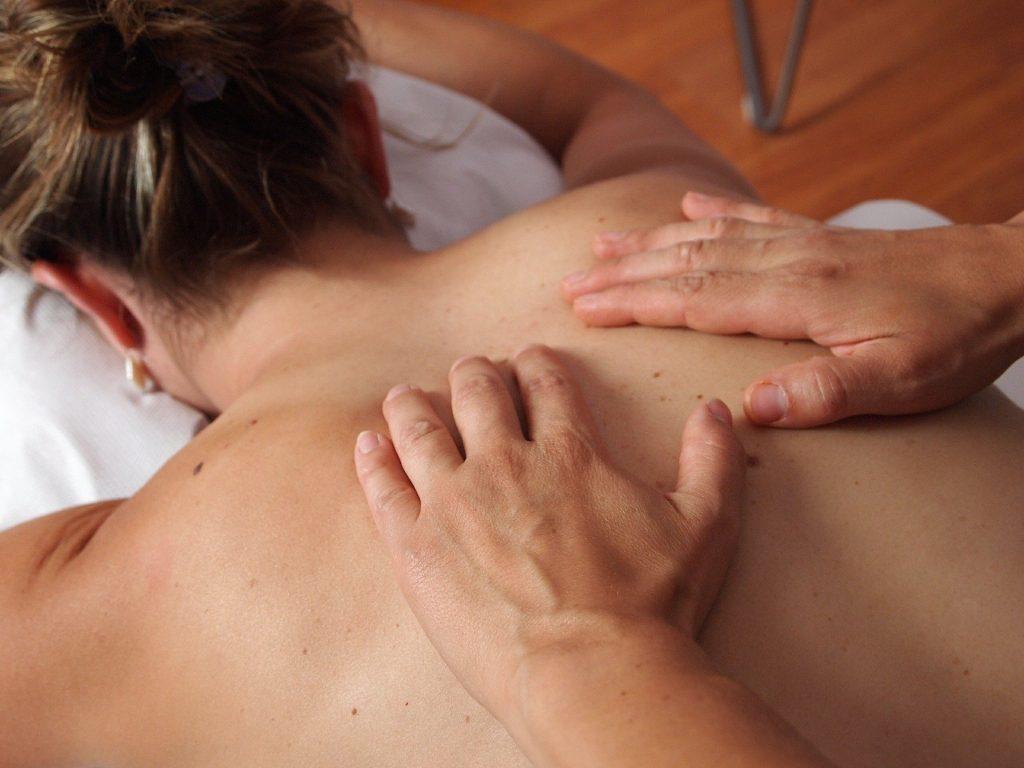 Imagem de uma mulher com os cabelos presos, deitada de costas sobre uma maca forrada com uma toalha na cor branca. Ela está recebendo um tratamento de quiropraxia em suas costas.