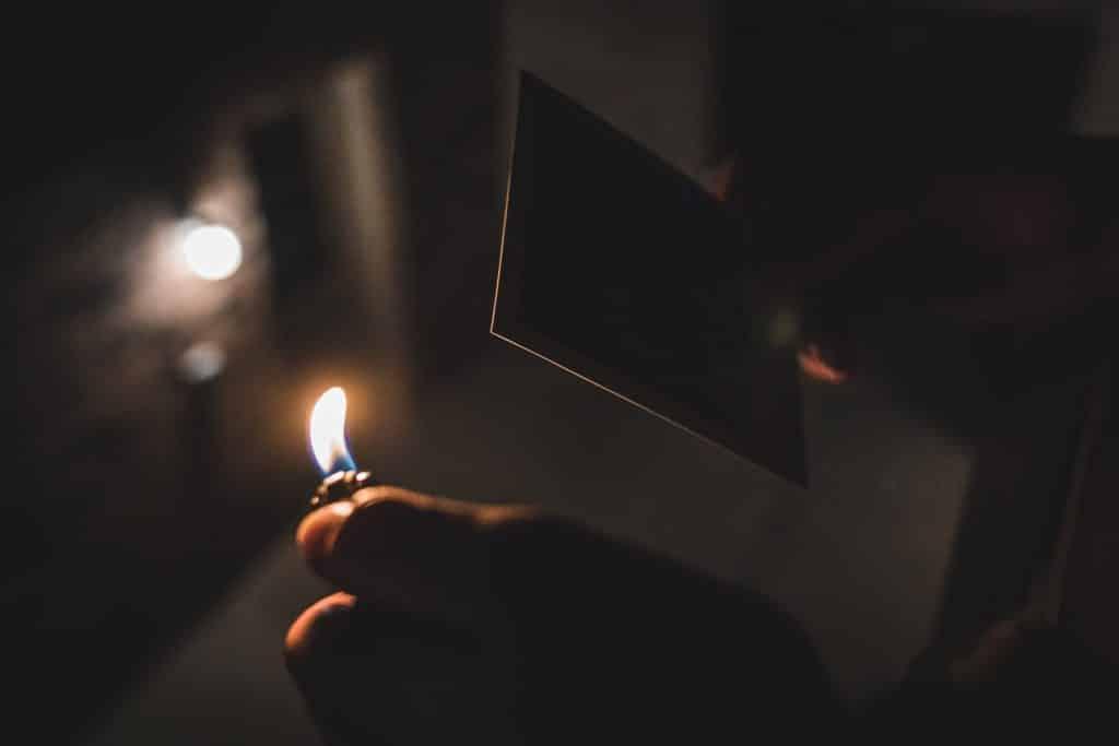 Pessoa queimando foto com um isqueiro.