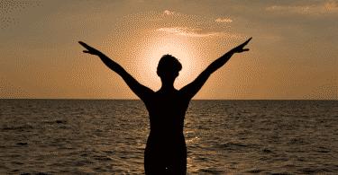 Silhueta de mulher com os braços erguidos na praia
