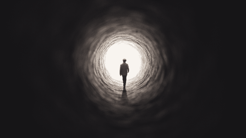 Silhueta de homem caminhando até a luz