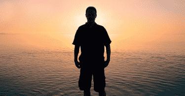 Silhueta de homem na praia observando o por do sol