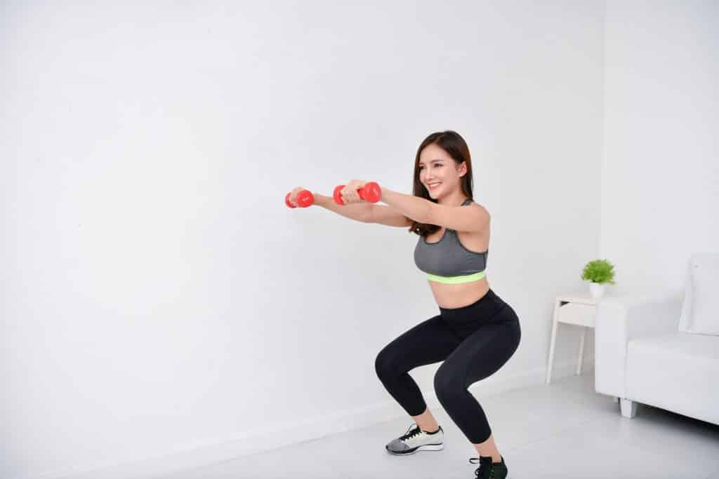 Mulher praticando atividade física em casa