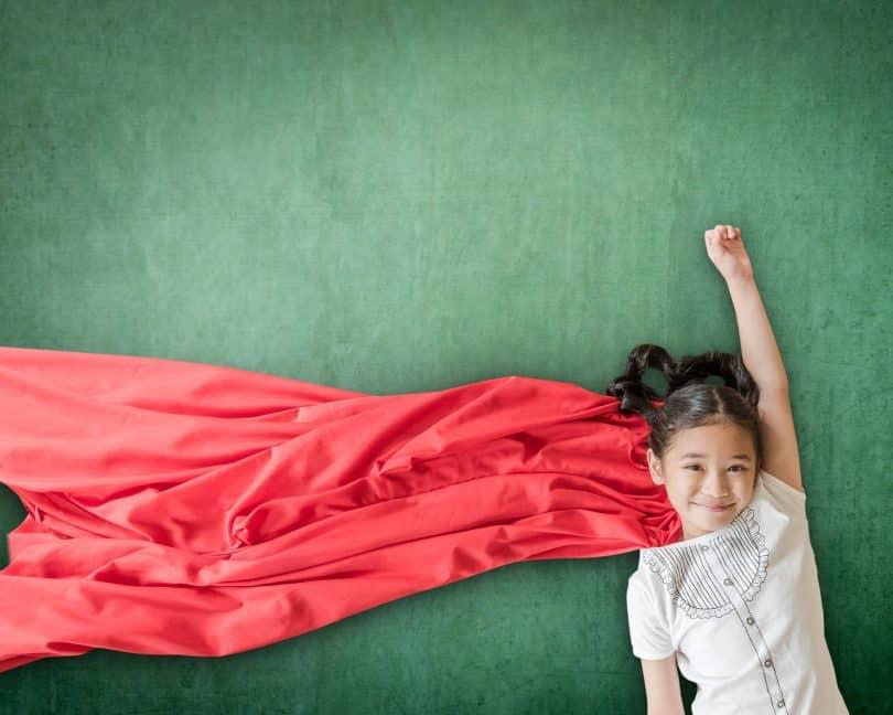 Garota deitada sobre cenário verde. Ela está com um dos braços erguidos e veste uma capa vermelha.