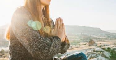 Mulher em prática meditativa em ambiente externo e solar, além de montanhoso.