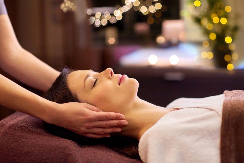Mulher branca recebendo massagem no rosto.