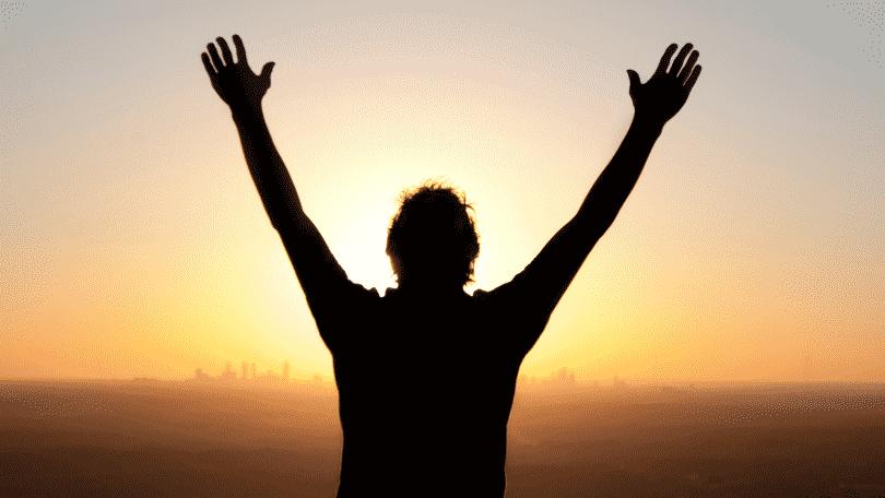 Silhueta de homem erguendo os braços para cima durante por do sol