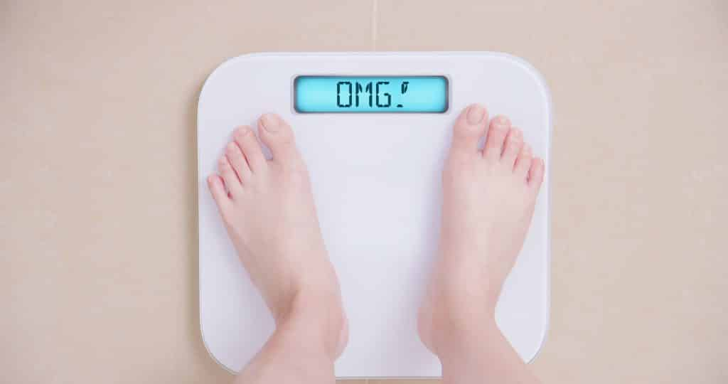 Conceito de perder peso com mulher em uma balança mostra OMG