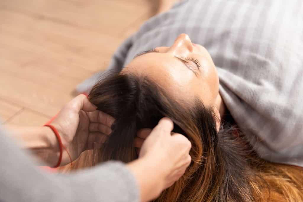 Mulher branca recebendo massagem na cabeça.