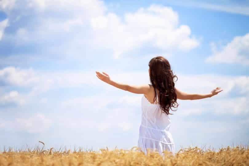 Mulher com os braços abertos e erguidos. Ela está em um campo.
