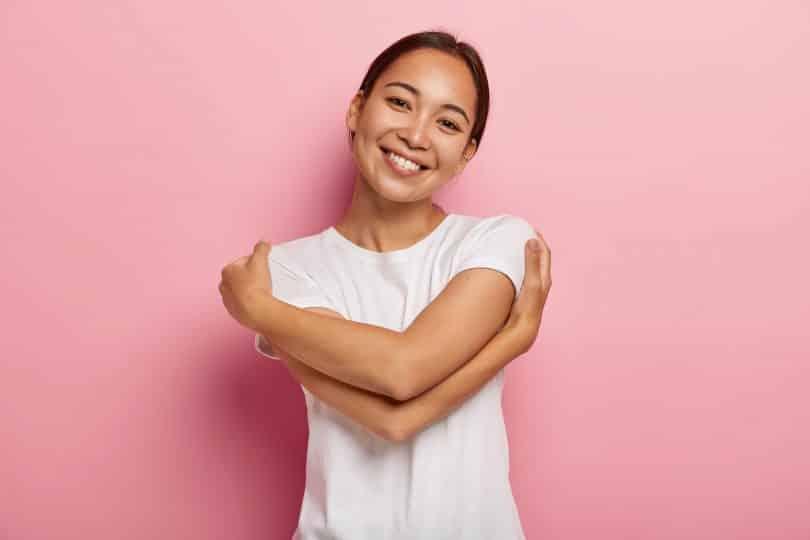 Mulher sorri e abraça a si mesma em fundo rosa.
