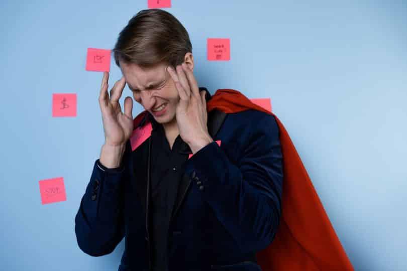 Homem pressiona as têmporas e possui o semblante de quem tem dor. Ele está com uma capa vermelha e, atrás dele, há post-its em uma parede azul.