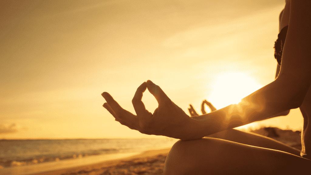 Pessoa meditando na praia