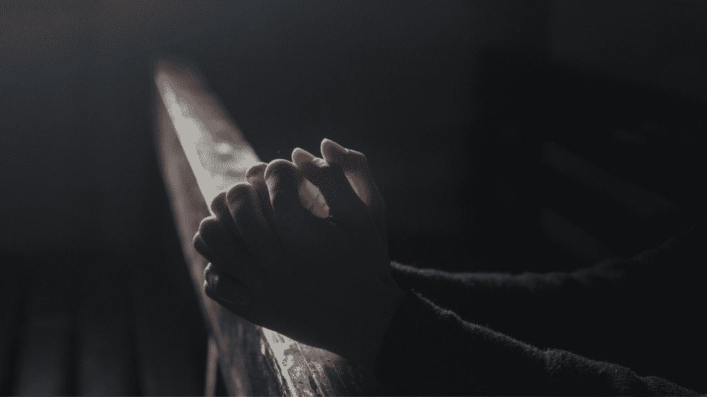 Mãos de pessoa orando no escuro