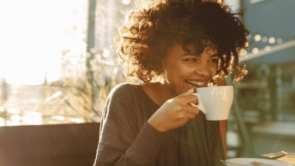 Mulher feliz tomando uma xícara de café